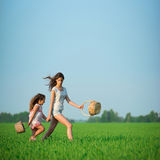 Young happy girls running witch baskets at green wheat field Stock Photos