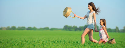 Young happy girls running witch baskets at green wheat field Royalty Free Stock Photography