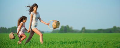 Young happy girls running witch baskets at green wheat field Royalty Free Stock Image