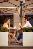 Young happy gorgeous lady is sitting in light cafe`s terrace outdoors on a sunny day and flirt with her leg with partner, while sm. Iling, looking at him Royalty Free Stock Photo