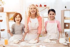 Young happy grandmother together with little happy grandchildren knead dough for cookies in kitchen. stock photo