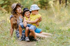 Young happy grandmother with two grandchildren sitting on a fore stock photography