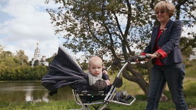 Young happy grandmother walks with my little grandson, sitting in a wheelchair. In the background, a meadow and a Church stock footage