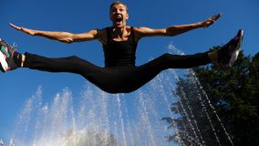 A young happy guy dancing modern ballet and wacking on a background of a fountain in a summer park. Slow-mo