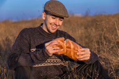 Young happy guy eats fresh bread outdoor. On sunset Stock Images