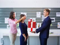 Beautiful young brunette and handsome man with a big gift for colleague. Business concept. stock photo