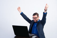 Young happy guy at a laptop. Young businessman sitting at a laptop Royalty Free Stock Photography