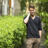 Young happy guy outdoors talking on a cell phone. High spirits. Royalty Free Stock Image