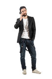 Young happy guy talking on the cellphone wearing cap Royalty Free Stock Photography