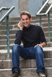 Young happy guy talking on mobile while sitting on outdoor stairs. Young guy talking on mobile while sitting on outdoor stairs Royalty Free Stock Images