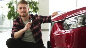 Happy handsome man posing with his new auto showing car keys to the camera royalty free stock photos