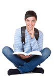 Young happy handsome male student reads study book. Close-up of handsome male student sitting on floor with satchel on back and study book in hands. Isolated on Royalty Free Stock Photo