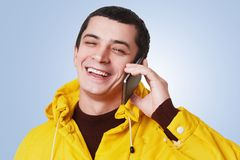 Young happy handsome man has phone conversation, talks with best friend, discuss something with glad expression, glad to hear him,. Wears yellow anorak isolated Royalty Free Stock Images