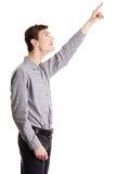 Young happy handsome man pointing up Stock Photography