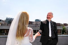 Young happy handsome wedding couple stands on the roof. Wedding concept. Young happy handsome wedding couple stands on the roof of the building. The groom Royalty Free Stock Image