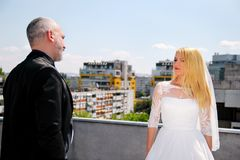 Young happy handsome wedding couple stands on the roof. stock image
