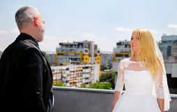 Young happy handsome wedding couple stands on the roof. stock images