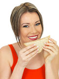 Young Happy Healthy Woman Eating a Salmon and Cucumber Brown Bread Sandwich Stock Images