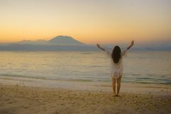 Young happy and healthy woman spreading arms free standing on sand beach looking at horizon sea water and volcano landscape on the stock photos