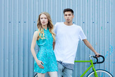Young happy hipster couple in love meet each other and dating whis bicycle. Pretty blonde caucasian woman with her hispanic boyfri Stock Photos