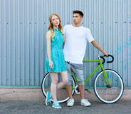 Young happy hipster couple in love meet each other and dating whis vintage bicycle. Pretty blonde caucasian woman with her hispani Royalty Free Stock Image
