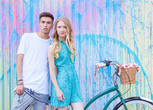 Young happy hipster couple in love meet each other and dating whis vintage bicycle. Pretty blonde caucasian woman with her hispani Royalty Free Stock Photography