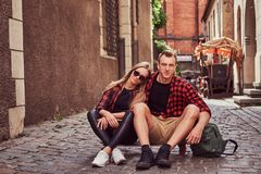 Young happy hipster couple, rest during a walk sitting on the pavement in the old Europe street. Young happy hipster couple, rest during a walk sitting on the Stock Images