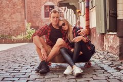 Young happy hipster couple, rest during a walk sitting on the pavement in the old Europe street. Young happy hipster couple, rest during a walk sitting on the Royalty Free Stock Photography