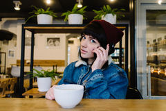 Young happy hipster girl talking on the phone and drinking coffee in a nice cafe. Young happy hipster girl in a cap and a blue denim jacket talking on the phone Royalty Free Stock Photos