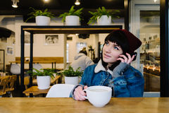 Young happy hipster girl talking on the phone and drinking a hot drink in cafe. Young happy hipster girl in a cap and a blue denim jacket talking on the phone Royalty Free Stock Photos