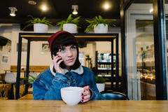 Young happy hipster girl talking on the phone and drinking tea in a beautiful cafe. Young happy hipster girl in a cap and a blue denim jacket talking on the Stock Photos