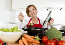 Young happy home cook woman in red apron at domestic kitchen holding saucepan tasting hot soup Royalty Free Stock Image