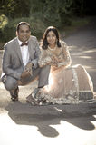Young happy Indian couple sitting together outdoors Stock Photos