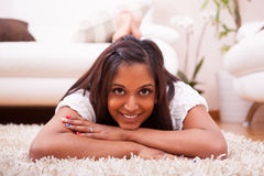 Young happy indian woman lying down on the floor Stock Photo
