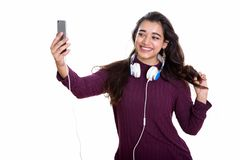 Young happy Indian woman smiling while wearing headphones around stock photos