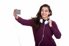 Young happy Indian woman smiling while wearing headphones around stock image