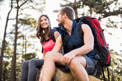 Young happy joggers sitting on rock and looking away Royalty Free Stock Photo