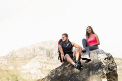 Young happy joggers sitting on rock Royalty Free Stock Photo