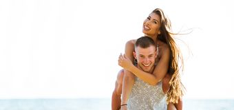 Young happy and joyful Caucasian adult romantic couple doing piggyback - Boyfriend carrying girlfriend on beach - with copy space. Young happy and joyful stock photo