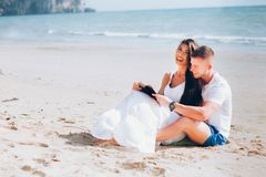 Young happy and joyful Caucasian adult romantic couple in white summer wear - Boyfriend and girlfriend reading a book together. On tropical beach stock photo