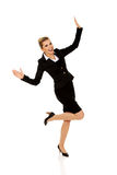Young happy jumping businesswoman. With hands up Stock Image