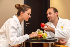 Young happy just married Caucasian couple in white bathrobes having fruits after spa on honeymoon. Man offers an apple to the woma royalty free stock photography