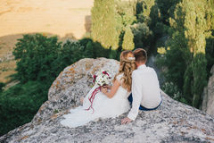 Young happy just married couple posing on the top of the mountain. Wedding day Stock Photo