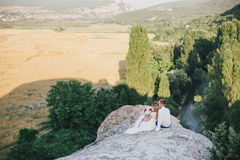 Young happy just married couple posing on the top of the mountain Stock Image