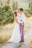 Young happy just married couple posing on the top of the mountain Stock Photo