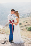 Young happy just married couple posing on the top of the mountain Royalty Free Stock Photography