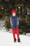 Young happy kid standing on the top of mountain in snowy winter. Young kid standing on the top of mountain in snowy winter Stock Photography