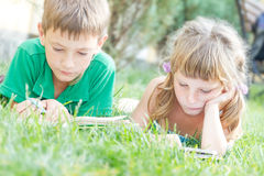 Young happy kids, children reading books on natural backgrou Royalty Free Stock Images