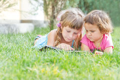 Young happy kids, children reading books on natural backgrou
