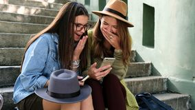 Two girlfriends doing online shopping in the park. Young happy ladies use smartphone for internet shopping stock video